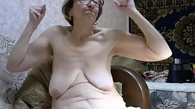 Saggy titted granny flexes her biceps on cam